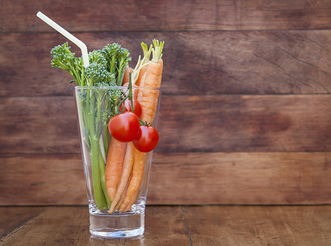 Glass of broccoli, carrots and tomato with straw